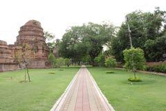 Pink-yellow brick road in Wat Chaimonkol. Around with ruined pakoda green atmosphere royalty free stock photos