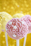 Pink and yellow cake pops decorated with sprinkles. Stock Image