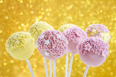 Pink and yellow cake pops decorated with sprinkles. Royalty Free Stock Photos