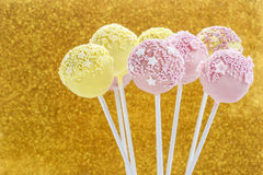 Pink and yellow cake pops decorated with sprinkles. Royalty Free Stock Photography