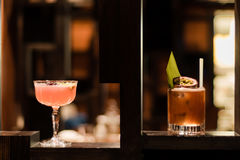 Pink and yellow cocktails garnished with fig and flowers. Alcoholic drinks in bar, in margarita and old fashioned glasses stock image