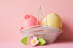 Pink and yellow Easter eggs in a basket with pink flower Royalty Free Stock Images