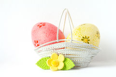 Pink and yellow Easter eggs in a basket with yellow flower Stock Images