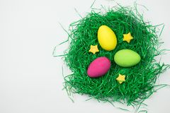 Pink, yellow and green Easter egg in green artificial grass on white background. royalty free stock image