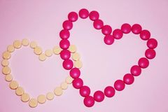 Pink and yellow heart-shaped vitamins stock images