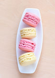 Pink and yellow macaron on a plate Stock Photos