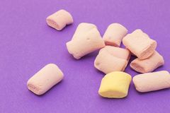 Pink and yellow with marshmallows. On violet background Royalty Free Stock Photography