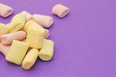 Pink and yellow with marshmallows. On violet background royalty free stock images