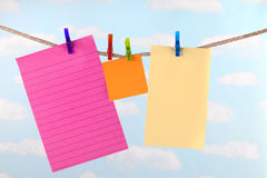 Pink, yellow  and orange note paper on clothesline Stock Photo
