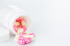 Pink and yellow pearl pills an pill bottle on white background Royalty Free Stock Image