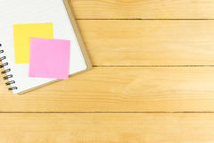 Pink and yellow post it on blank notepad on table. Pink and yellow post it on blank notepad on wooden table Royalty Free Stock Photos