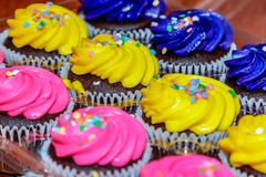 Pink, yellow and purple cupcakes ready for the party. Stock Photo