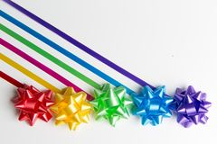Pink,yellow,red,green,blue and purple gift wrap bows with diagonally placed ribbons top view on white background stock photo