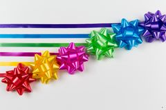 A top view of pink,yellow,red,green,blue and purple gift wrap bows with ribbons on a white background. stock image