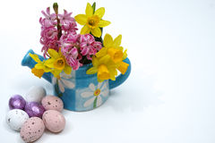 Pink and yellow spring flowers in blue water kan, colored eggs, Royalty Free Stock Photography