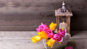 Pink and yellow  spring tulips  in box and candle in lantern  on. Spring tulips  in box and candle in lantern  on vintage  wooden background. Selective focus Stock Photo