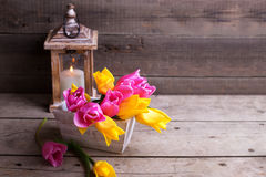 Pink and yellow  spring tulips  in box and candle in lantern  on. Spring tulips  in box and candle in lantern  on vintage  wooden background. Selective focus Royalty Free Stock Images