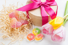 Pink yellow tulips and gift box with red ribbon. Sweet hearts on a white painted wooden background. Top view with copy space Royalty Free Stock Image