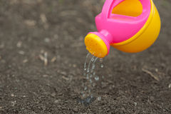 A pink yellow watering can water the ground. Drops of water spill, dissipate moisturize the earth. Help fight the drought. Royalty Free Stock Photography
