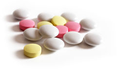 Pink, yellow and white tablets on a white background. stock photo