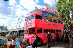 Pink yogurt truck South Bank London. Funny pink frozen yogurt truck and people relaxing on South Bank next to Golden Jubilee Bridge on summer Sunday,Central Stock Photo