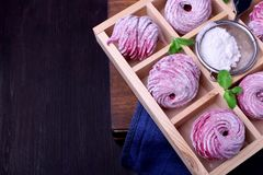 Pink zephyr covered in sugar powder in a wooden box. With cells stock photos
