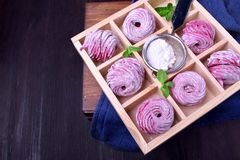 Pink zephyr covered in sugar powder in a wooden box. With cells stock photography