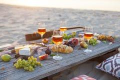 Pinkin na plaży przy zmierzchem w boho stylu, jedzeniu i napoju conc, zdjęcie royalty free