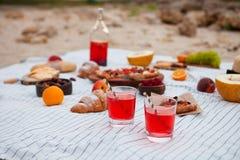 Pinkin na plaży przy zmierzchem w szkockiej kracie, jedzeniu i napoju białych, zdjęcie stock
