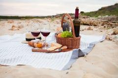 Pinkin na plaży przy zmierzchem w szkockiej kracie, jedzeniu i napoju białych, zdjęcia stock