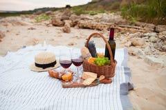 Pinkin na plaży przy zmierzchem w szkockiej kracie, jedzeniu i napoju białych, obrazy stock