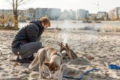 Pinkin z ogniskiem na plaży z psem obraz stock