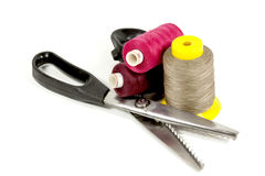 Pinking Shears With Three Reels Of Colored Cotton Stock Images