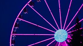 Pinklight ferris wheel on a dark blue background and with a tree in the front of stock images