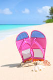 Pinks flip-flops on a sunny sandy beach.Tropical beach vacation Royalty Free Stock Photography