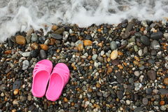 Pinky slippers on pebbles near water. Stock Images