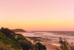 Pinky zmierzch w lato czasie na plaży w Ballina z widok na ocean i górkowatym krajobrazem, Byron b fotografia stock