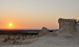 Pinnacle Desert Sunset: Nambung National Park, Western Australia. The Pinnacle Desert landscape and Indian Ocean orange sunset with limestone rock formations and Stock Photography