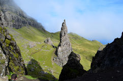 Pinnacle Rock on the Isle of Skye. Pinnacle rock formation with a light haze of clouds on surrounding hills Stock Images