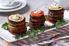 Pinnacles of baked tomato, zucchini, eggplant on a white plate Stock Photos
