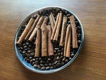Pinnar av kanel med kaffebönor i en metall bowlar på en trätabell royaltyfri fotografi