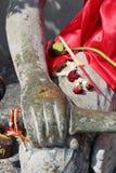 Pinnar av rökelse och torkade blommor förläggas på låret av en Buddhastaty (Thailand) royaltyfria bilder