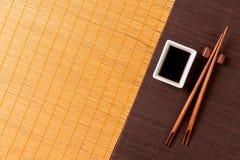 Pinnar och bunke med soya på matt blak för två bambu och gul bästa sikt med kopieringsutrymme arkivfoto
