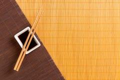 Pinnar och bunke med soya på matt blak för två bambu och gul bästa sikt med kopieringsutrymme arkivbilder
