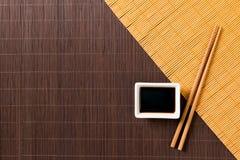 Pinnar och bunke med soya på matt blak för två bambu och gul bästa sikt med kopieringsutrymme arkivbild