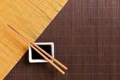 Pinnar och bunke med soya på matt blak för två bambu och gul bästa sikt med kopieringsutrymme royaltyfri bild