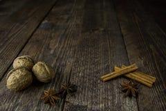 Pinnar och peppar för valnötanis kanelbruna på en träbakgrund Royaltyfri Fotografi