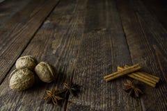 Pinnar och peppar för valnötanis kanelbruna på en träbakgrund Royaltyfri Foto
