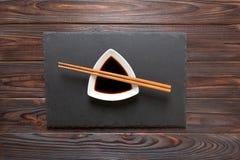 Pinnar och soya på svart stenar plattan, träbakgrund royaltyfri foto