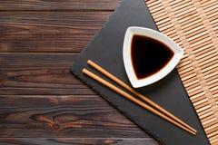 Pinnar och soya på svart stenar plattan, träbakgrund med kopieringsutrymme arkivbild